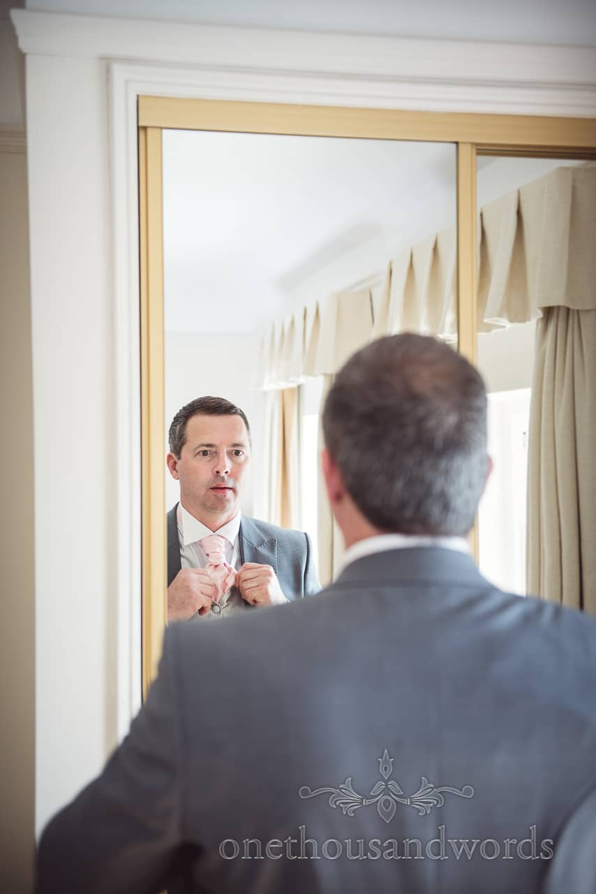 groom in grey wedding tail suit adjusts pink cravat in mirror on wedding morning