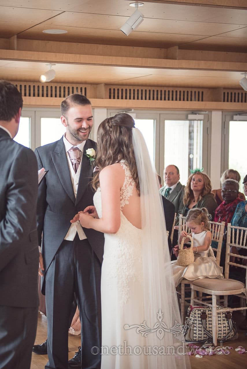 Groom in tails smiles during ceremony at Durlston Castle Wedding Photographs