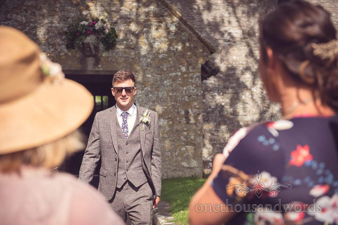 Groom in three piece grey tweed wedding suit in sunglasses outside church