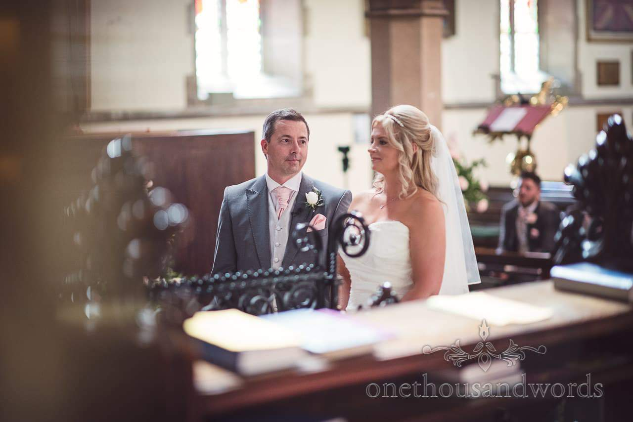Groom looks at bride during wedding service at St Peter's church in Bournemouth