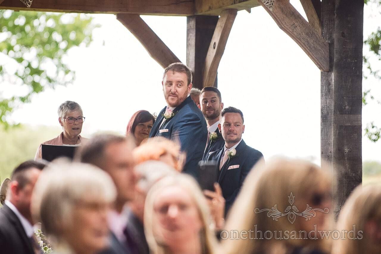 Groom looks back down the aisle as bride arrives at Coppleridge Inn Wedding