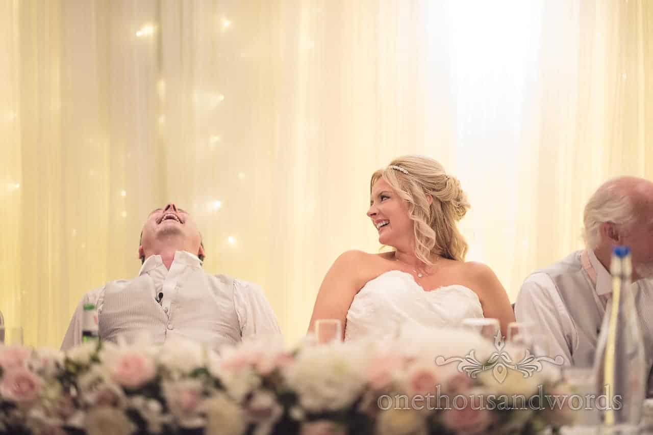 Groom nearly falls of his chair with laughter at best man's speech against LED backdrop