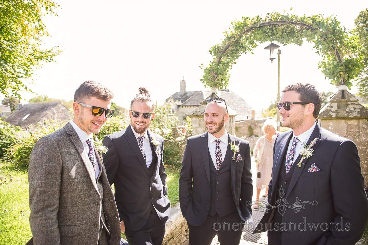 Grooms men in wedding suits and sunglasses outside church on sunny wedding morning