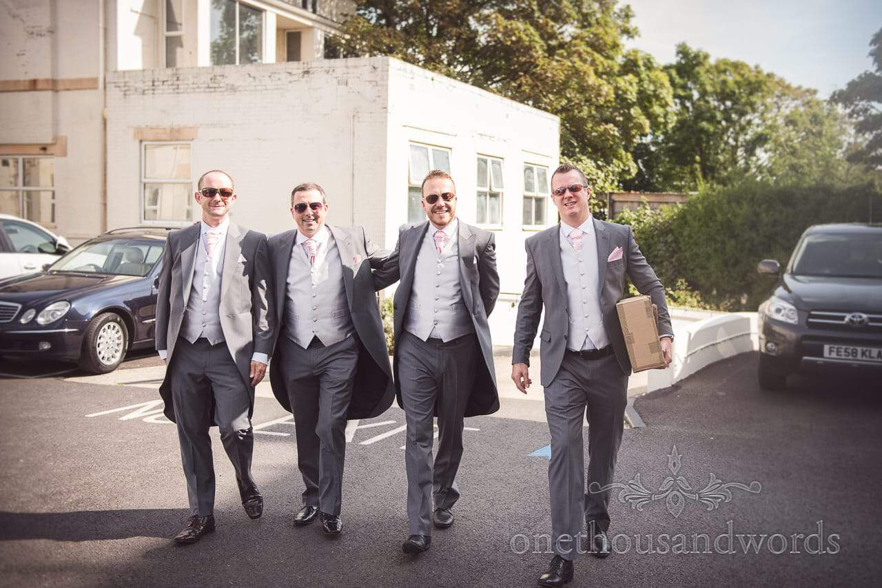 Grooms party in grey tail suits and sunglasses walk through Highcliff Marriott car park