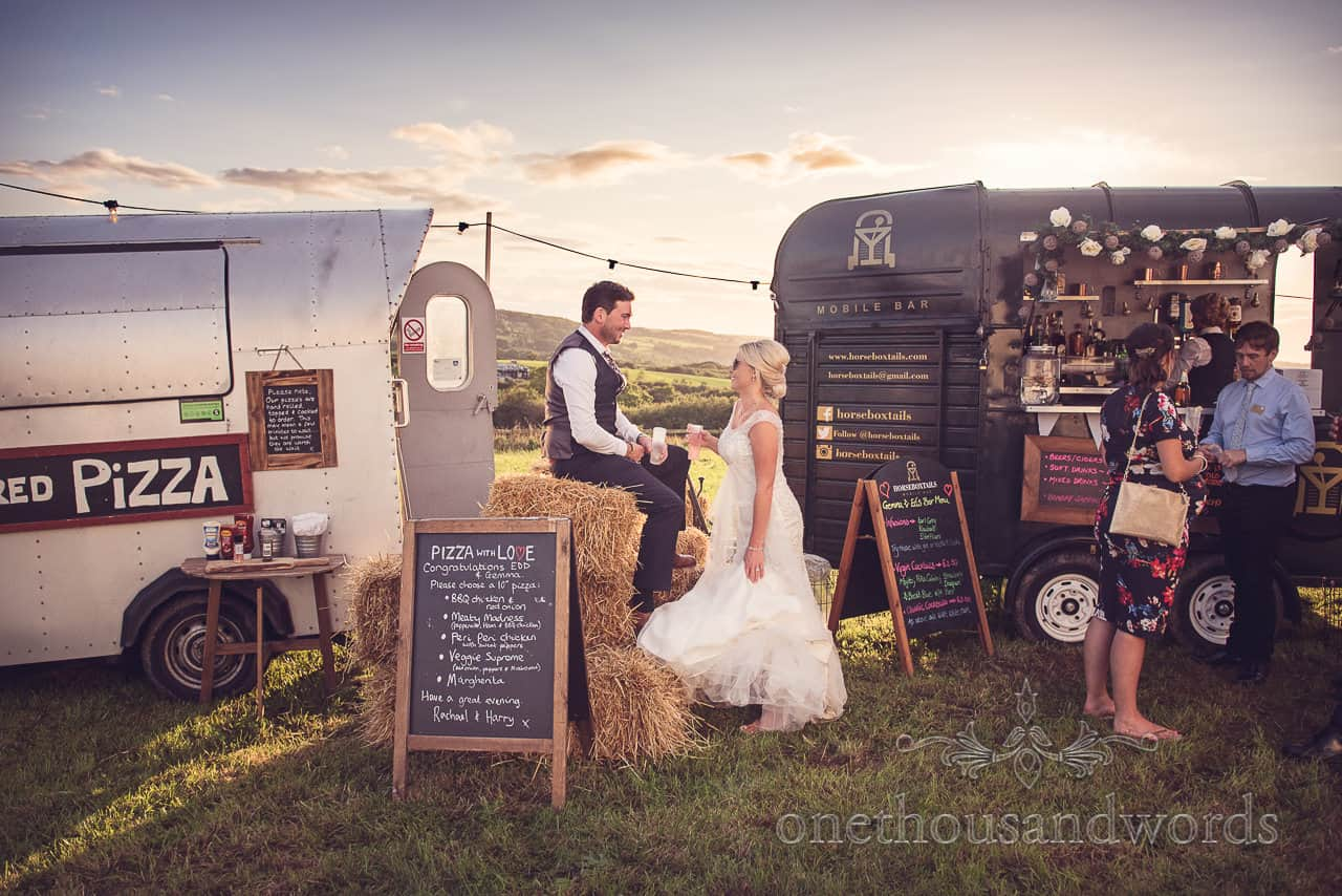 Groomsman and bride enjoy a drink at the mobile bar from Purbeck Valley Farm wedding photographs
