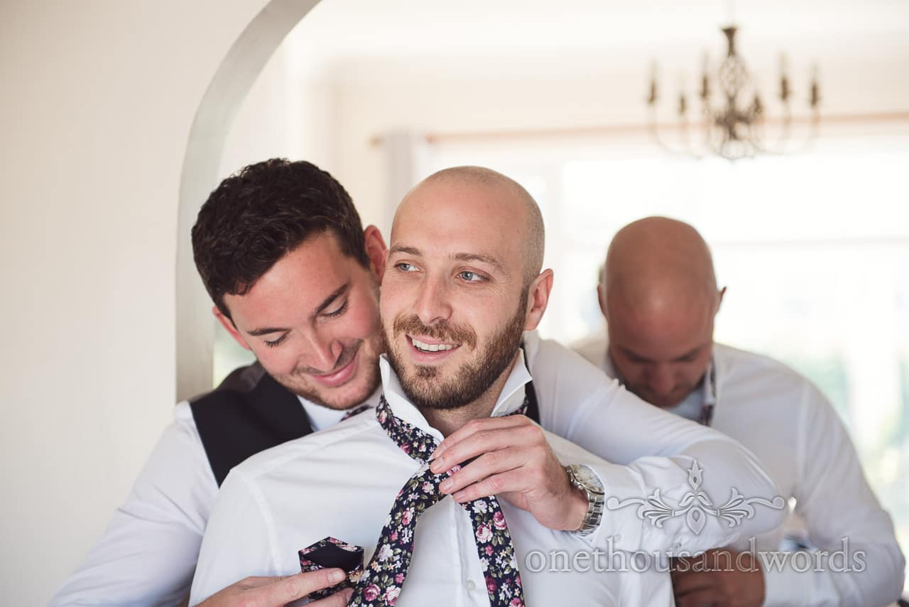 Groomsman had tie tied in an over friendly way during wedding morning preparations