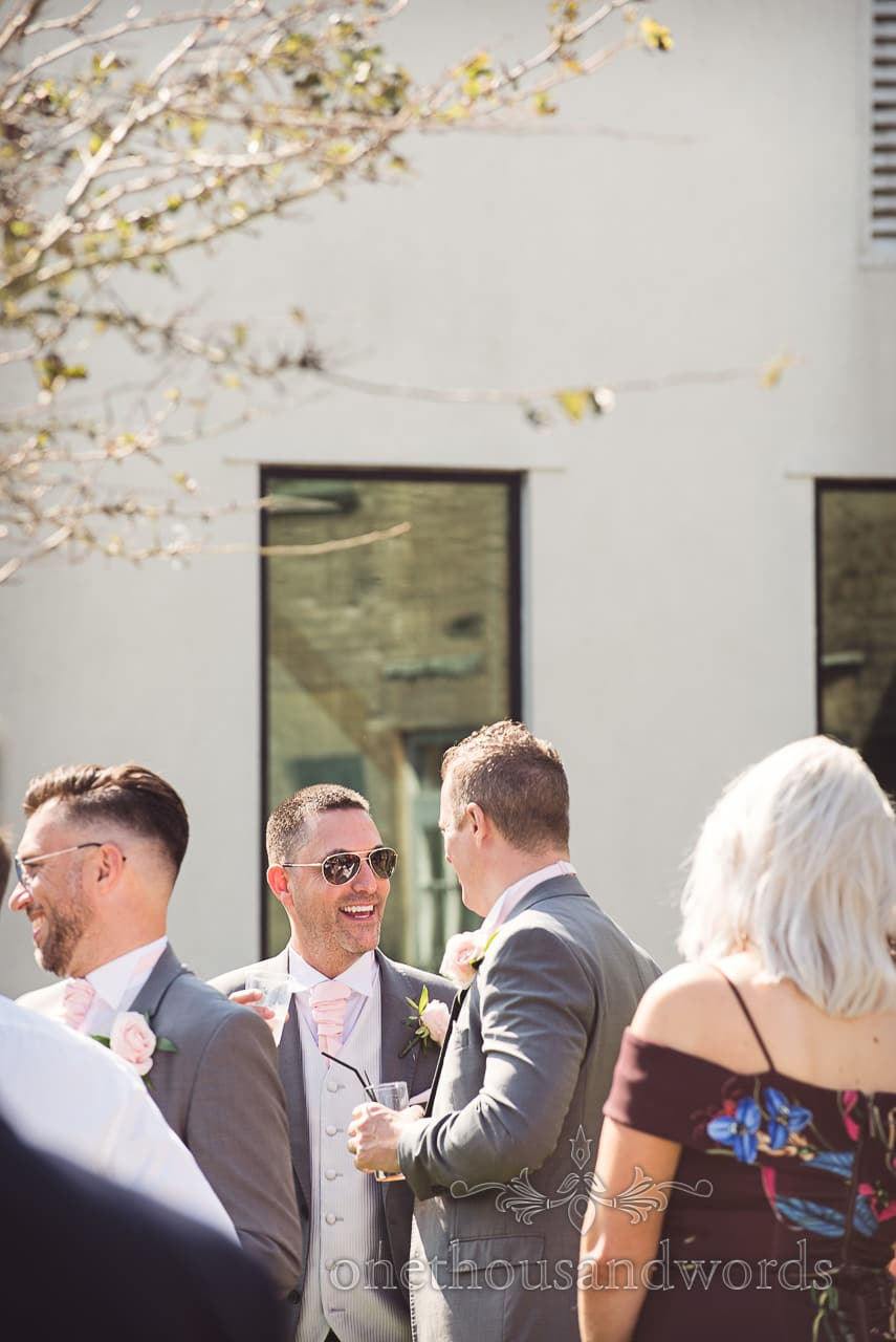 Groomsman in aviator sunglasses and grey suit at Bournemouth hotel wedding drinks reception