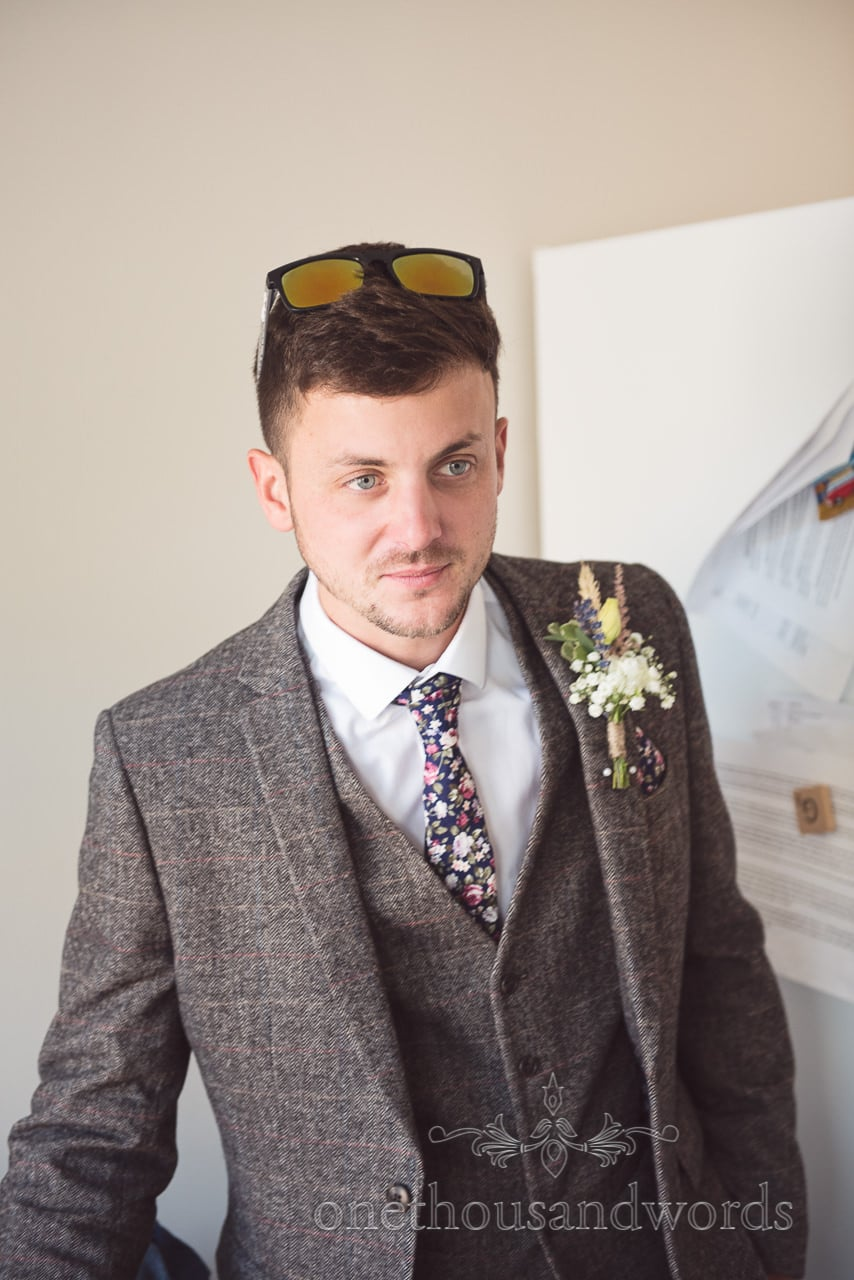 Groomsman in three piece tweed wedding suit with floral tie and sunglasses