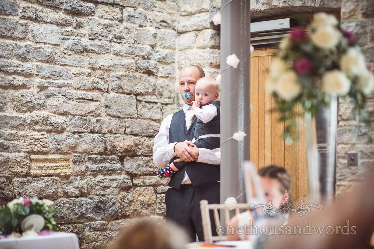 Groomsman listens to wedding speeches with a dummy in his mouth
