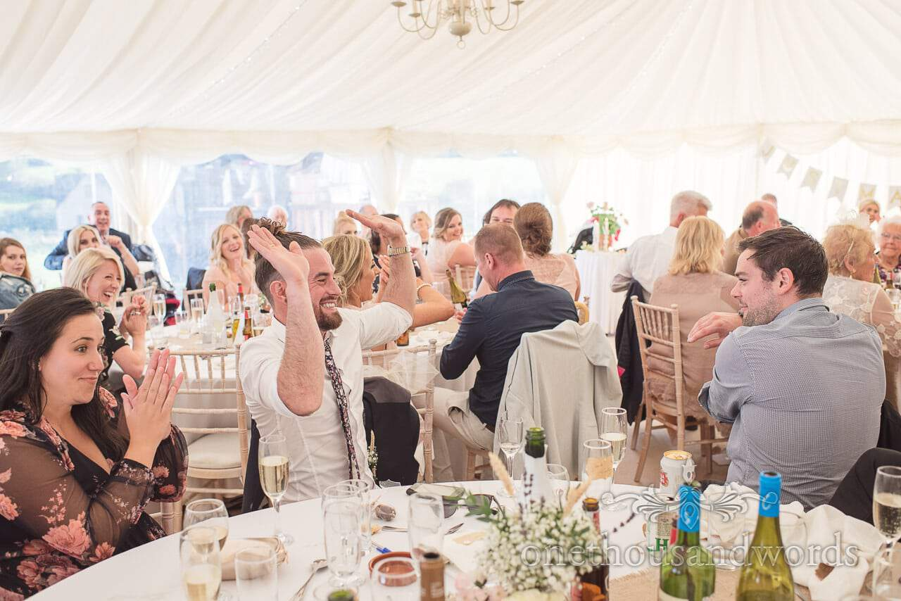 Groomsman takes round of applause at Purbeck Valley Farm wedding photographs