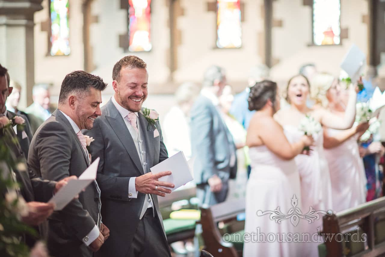Groomsmen laughing during wedding service at St Peter's Church Bournemouth