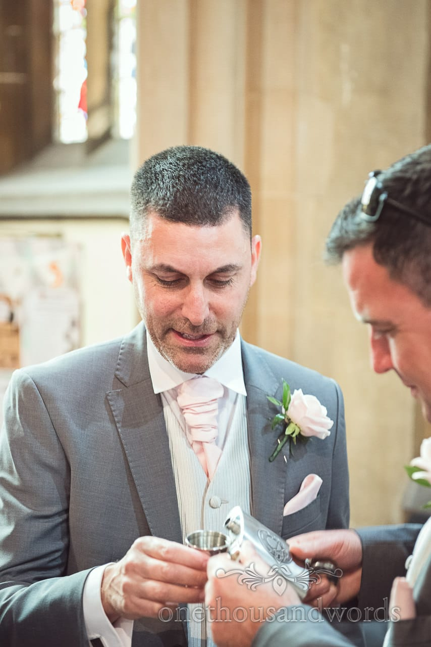 Groomsmen pour whiskey from hip flask in church on wedding morning in Bournemouth