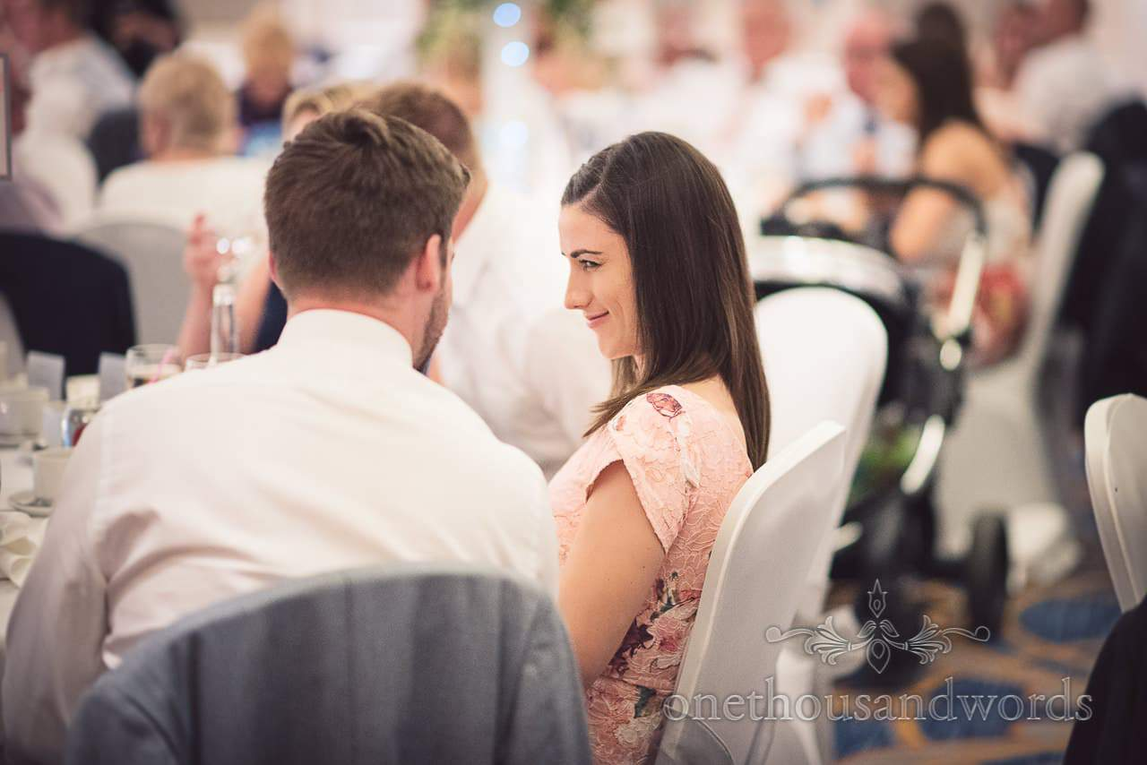 Guest makes silly face at partner during Bournemouth Marriott wedding breakfast