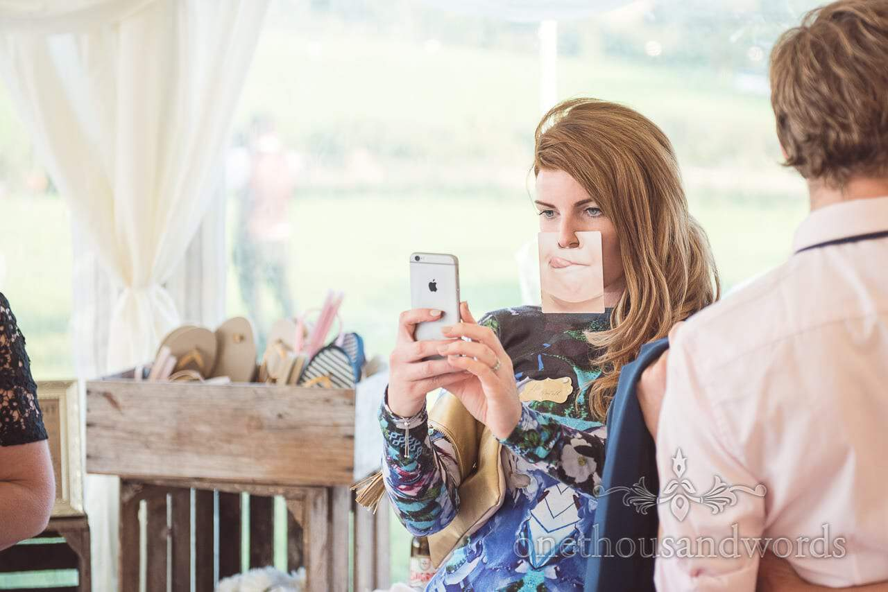 Guest takes a selfie with face mate prop at Purbeck Valley Farm wedding photographs