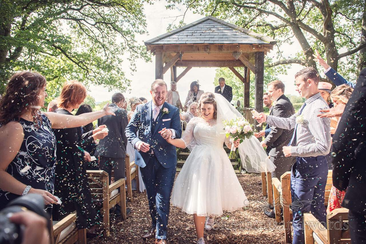 Guests throw confetti during woodland ceremony at Coppleridge Inn Wedding