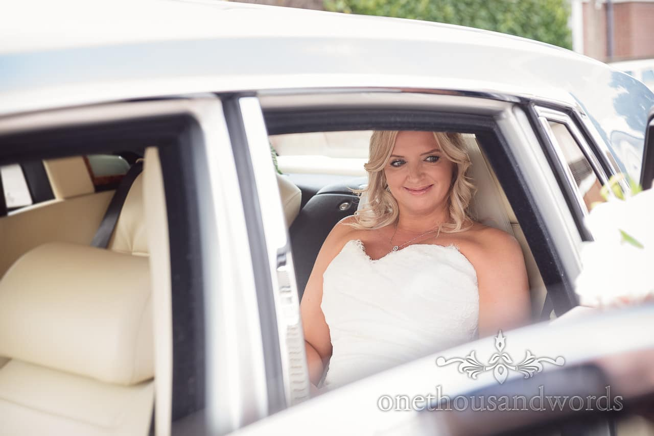 Happy bride looks through window of Bentley wedding car on way to church