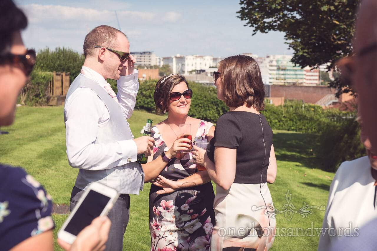 Happy wedding guests enjoy drinks reception overlooking Bournemouth in the sun