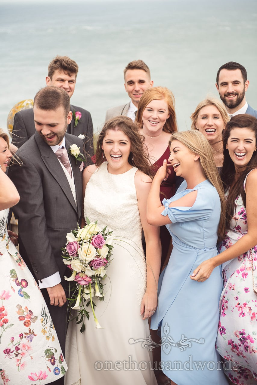 Laughter amongst group wedding photograph by the sea at Durlston Castle
