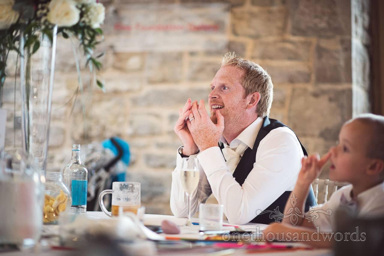Male wedding guests listens to wedding speeches at Durlston Castle Wedding