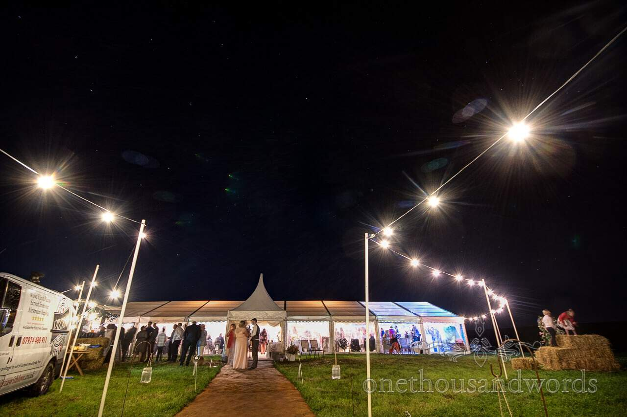 Marquee with festoon lights at Purbeck Valley farm wedding Photographs