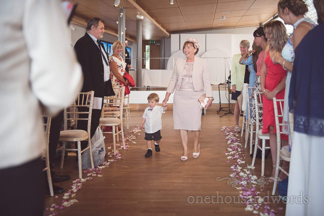 Mother of the bride walks page boy down aisle at Durlston Castle Wedding