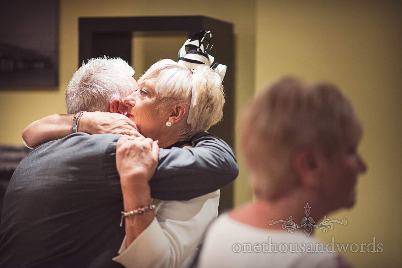 Mother of the groom hugs wedding guests during line up at Highcliffe Marriott wedding