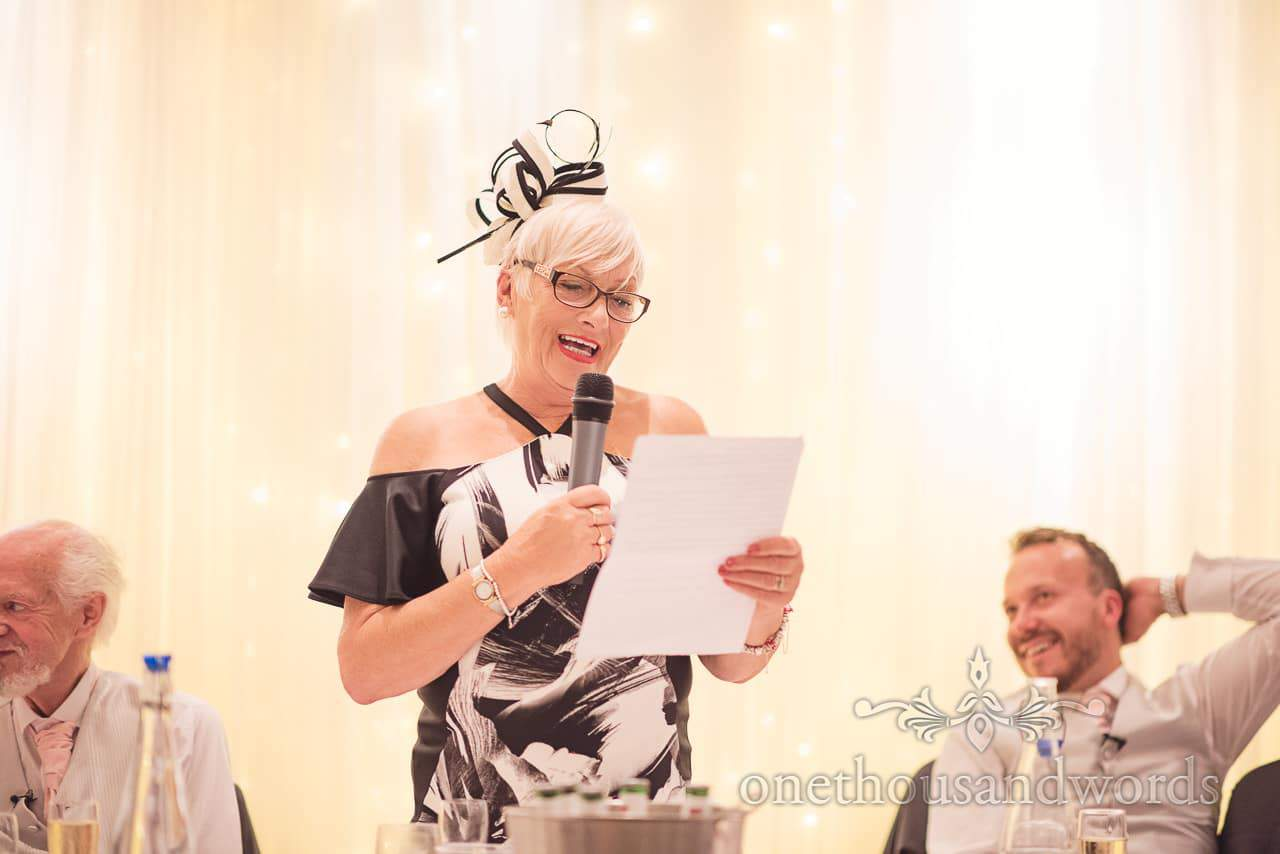 Mother of the groom in black and white dress and fascinator makes wedding speech