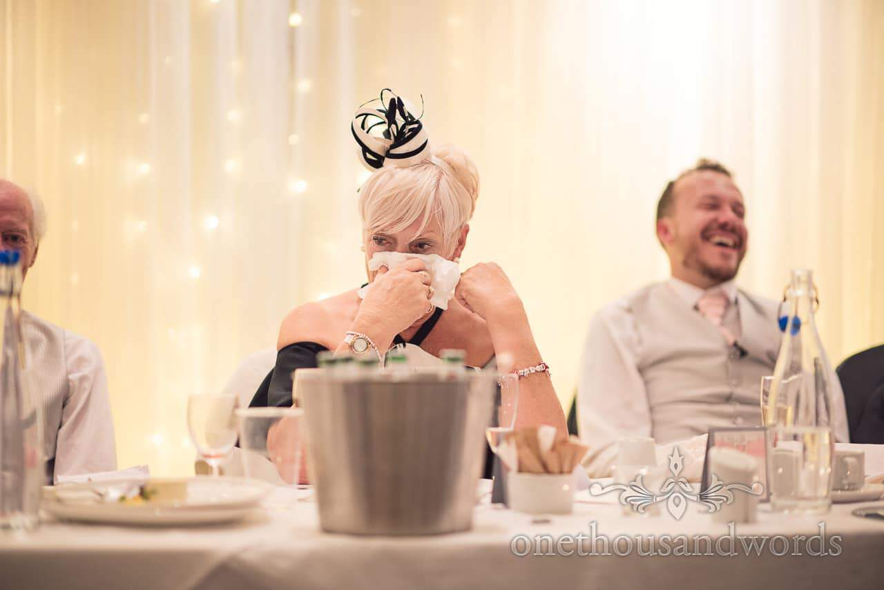 Mother of the groom wipes her tears away with tissue during wedding speeches