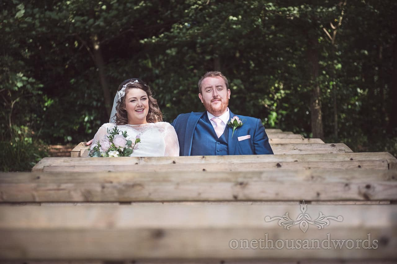 Newlyweds take a break on seating area in the woods at Coppleridge Inn Wedding Photographs