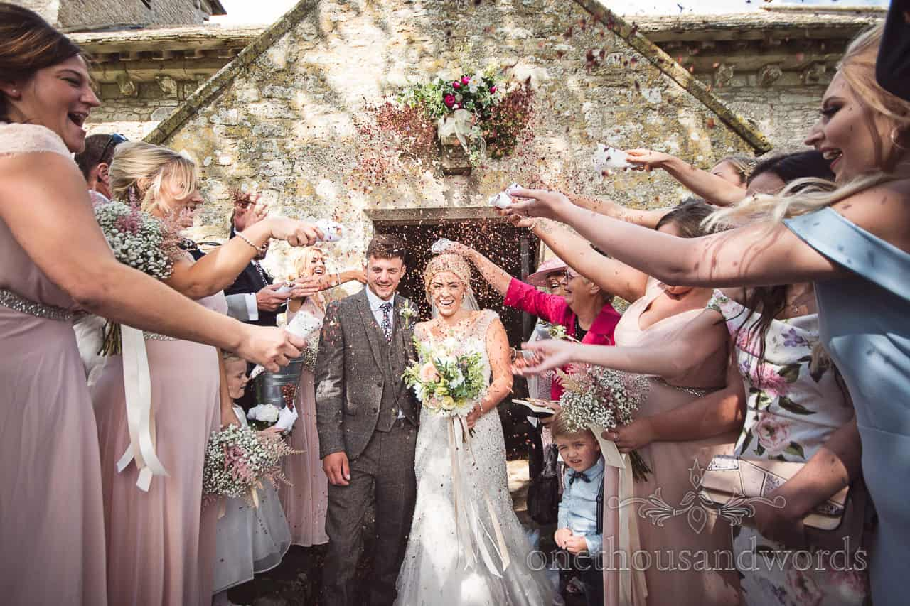 Newlyweds walk through shower of confetti outside church