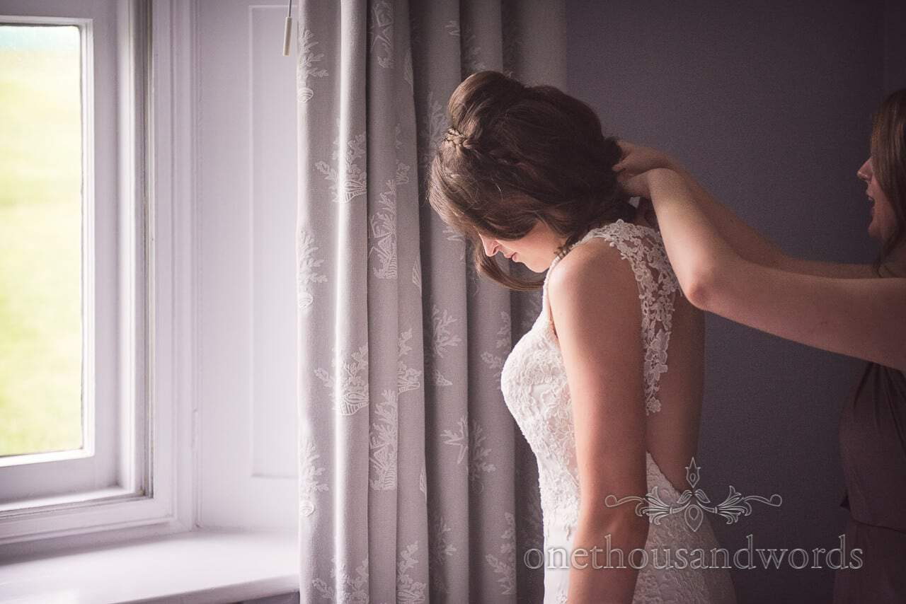 Photograph of bride being buttoned into wedding dress on wedding morning