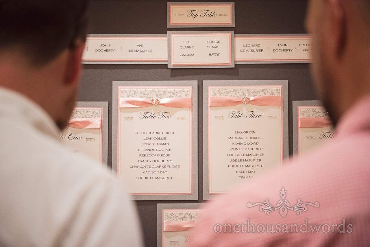 Pink and grey themed wedding table plan with diamantés and pink ribbons