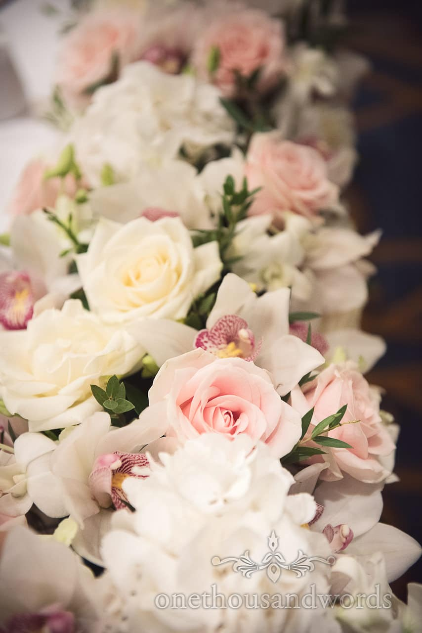 Pink roses in amongst white roses and orchids as top table wedding spray