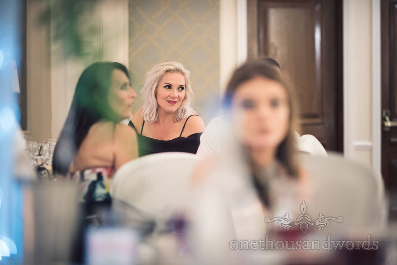Platinum blonde wedding guest smiles during wedding speeches at Bournemouth Hotel