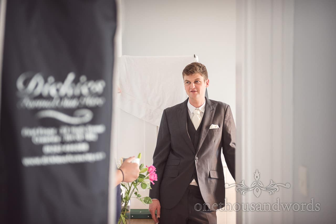 Portrait photograph of best man in grey suit with white tie on wedding morning