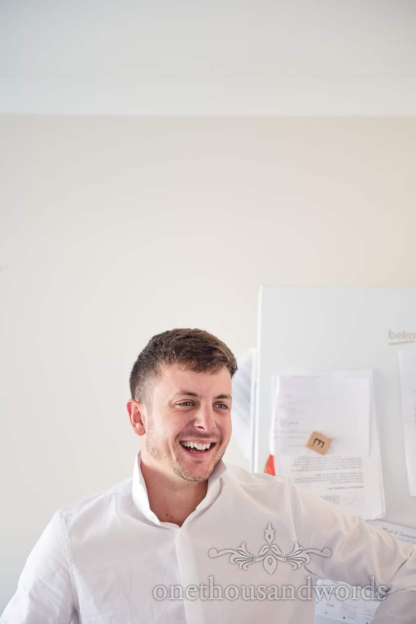 Portrait photograph of groom laughing on wedding morning preparations