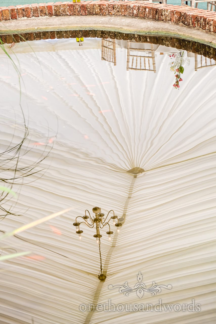 Reflection of marquee drapes in pond at Coppleridge Inn Wedding Photographs
