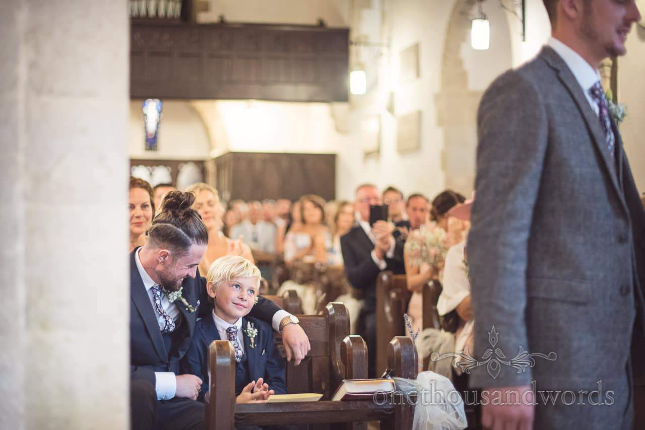Smiling son looks on parents say their vows