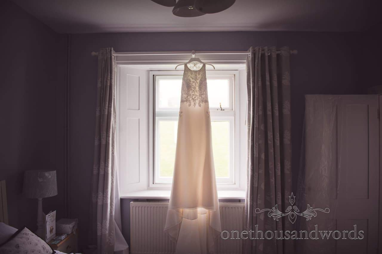 Stunning minimal detailed wedding dress hangs in the window on wedding morning