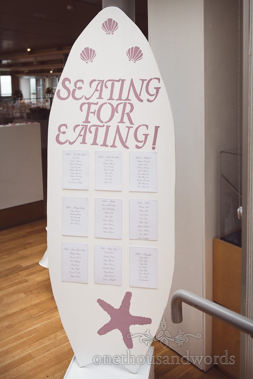 Surfboard shaped seating plan with shells and starfish at Durlston Castle Wedding