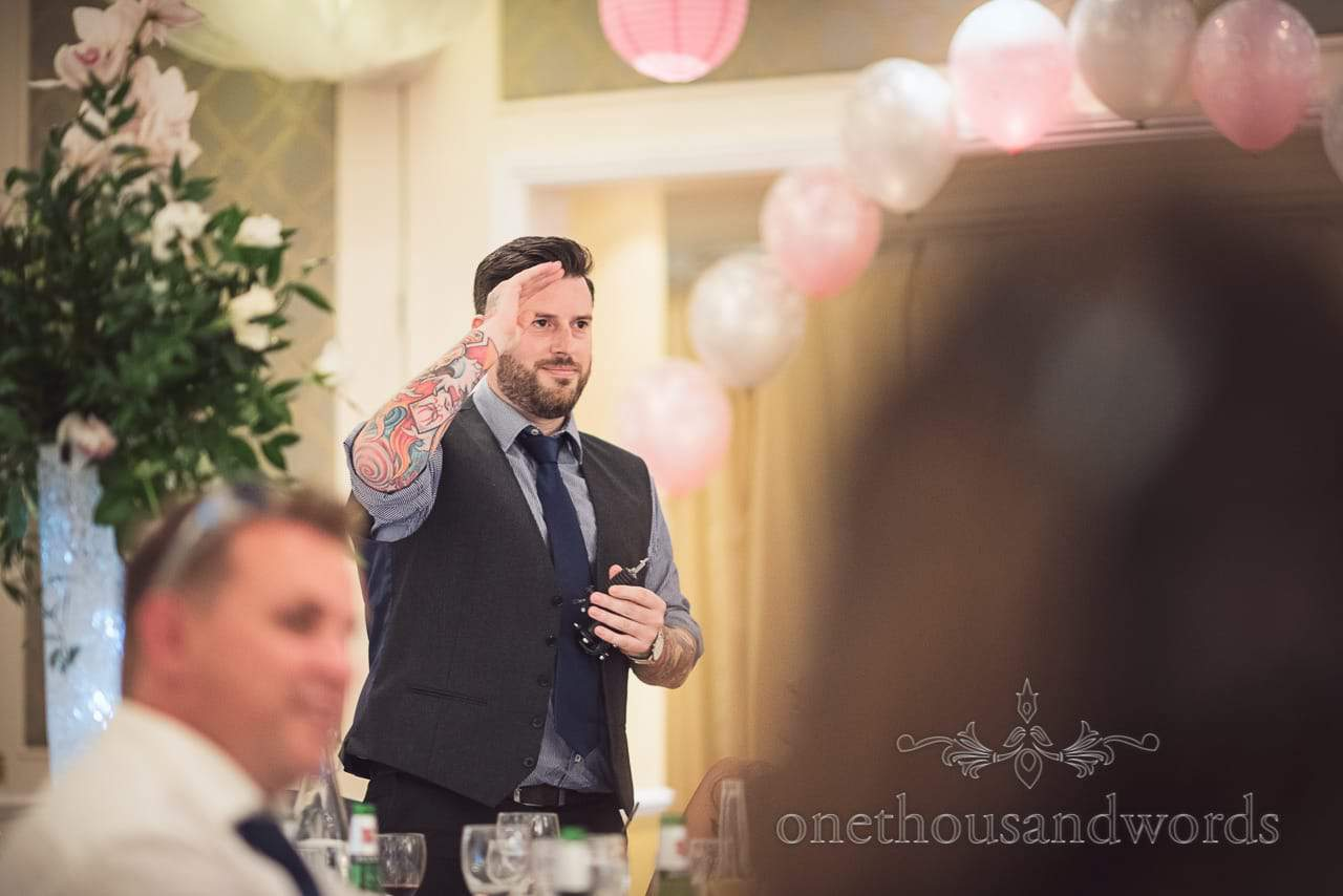 Tattooed man with tattoo machine salutes groom during wedding speech