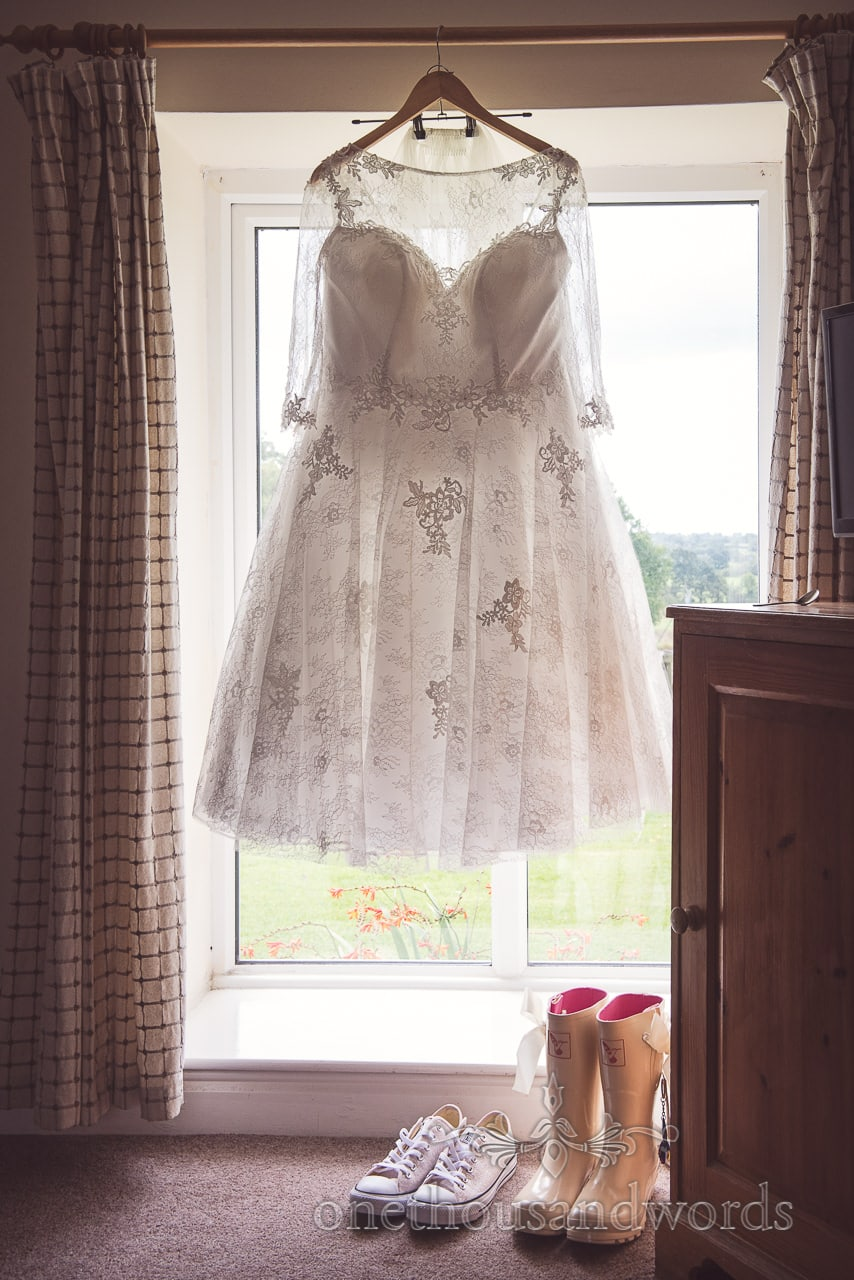 Tea length wedding dress with lace detail hangs in window at Coppleridge Inn Wedding