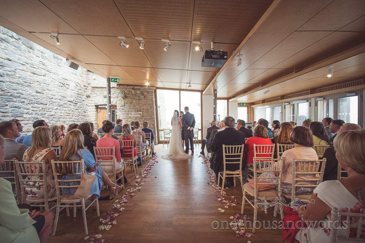 The gallery room with petals lining the aisle at Durlston Castle Wedding ceremony