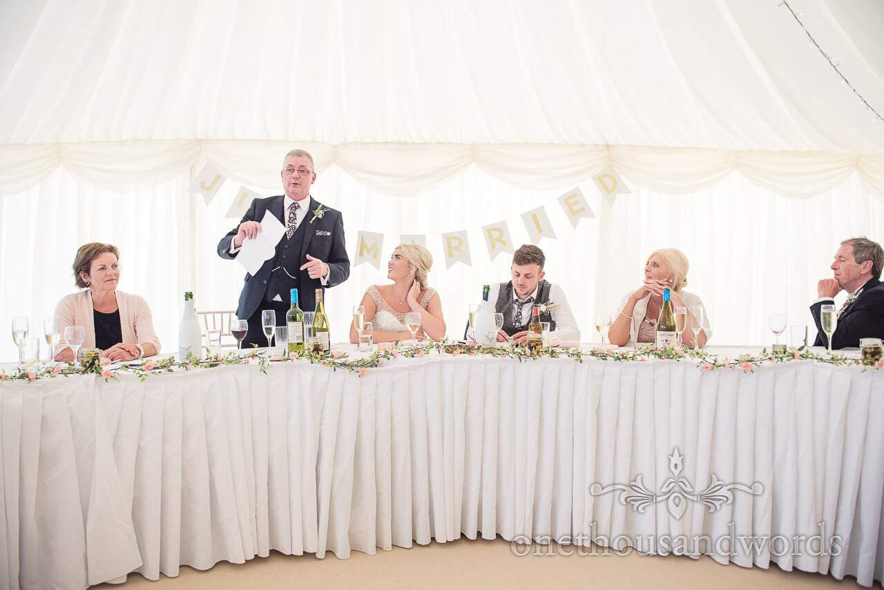 Top table during father of the bride speech at Purbeck Valley Farm wedding photographs
