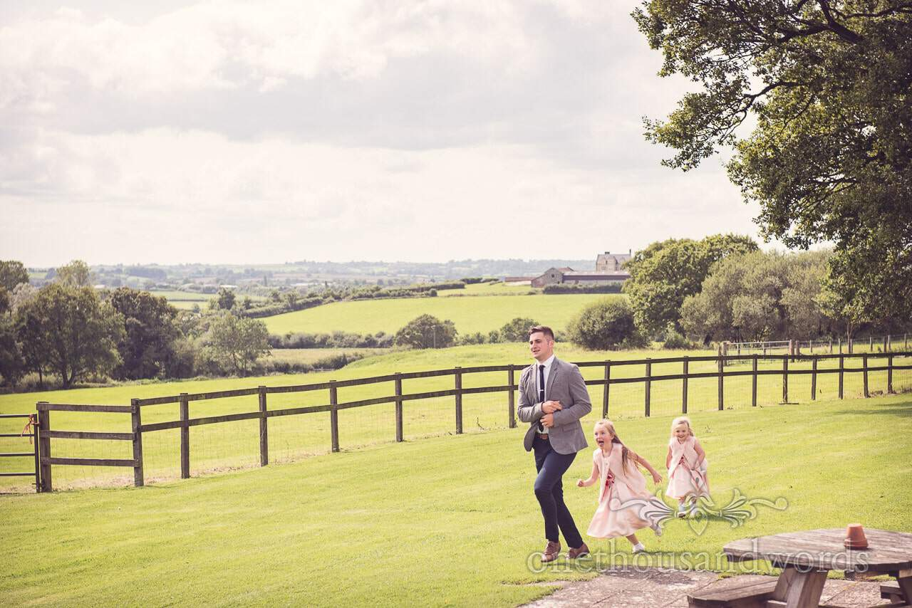 Two girls chasing guests in garden at Coppleridge Inn Wedding Photographs