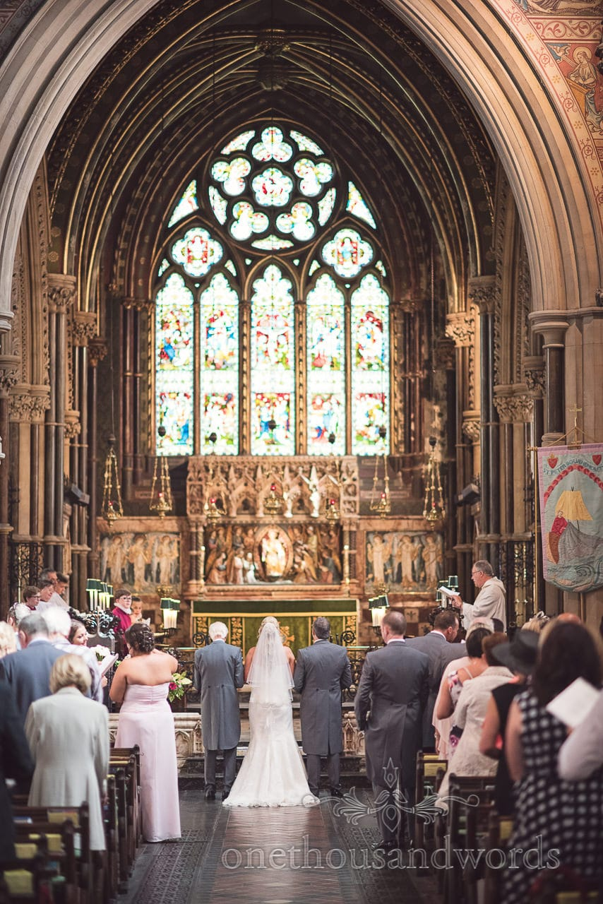 Wedding ceremony with stained glass windows and stone arches at St Peter's Bournemouth