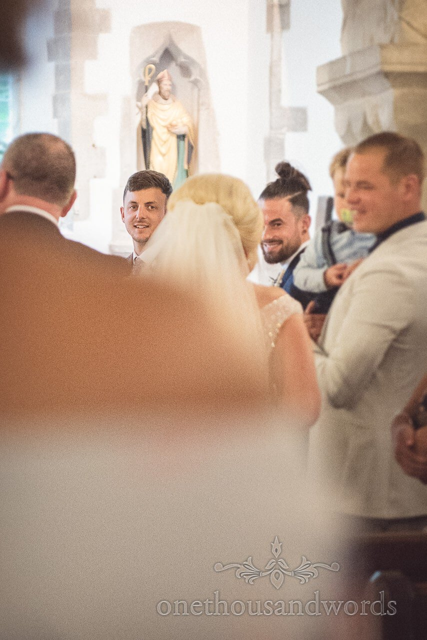 Wedding first look photograph of grooms face as he sees bride for first time in church