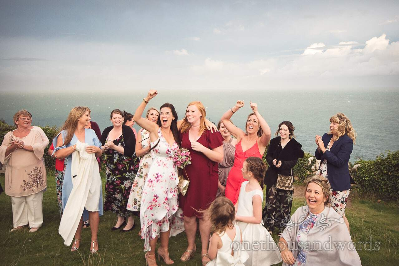 Wedding guest catches bride's bouquet at Durlston Castle Wedding by the sea