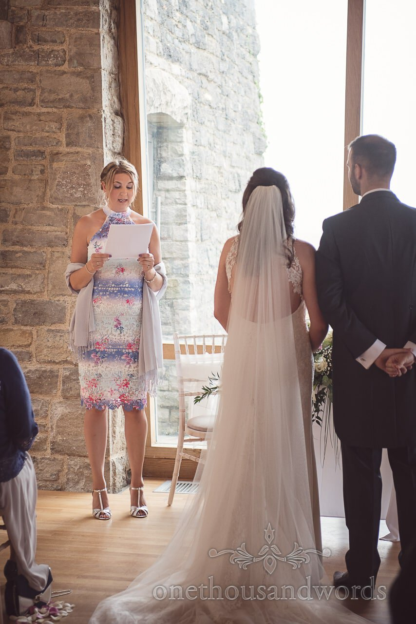 Wedding guest reads to bride and groom at Durlston Castle Wedding ceremony