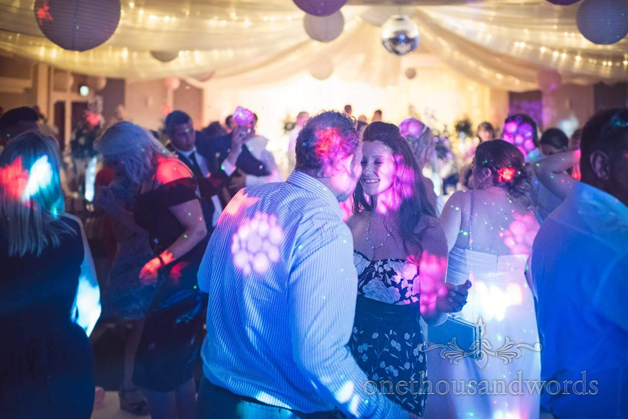 Wedding guests dance under blue lights at Bournemouth Highcliff Marriott wedding venue